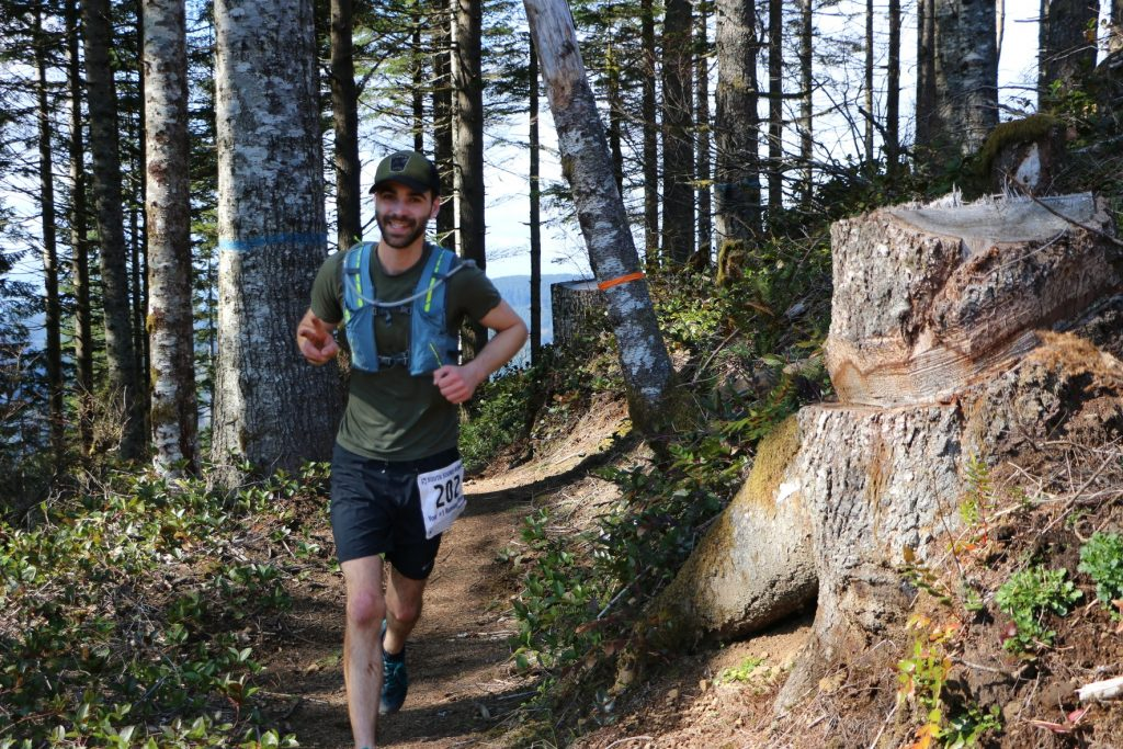 Chiropractor running a 25k trail run through the woods, wearing shorts, a t-shirt and a baseball cap, smiling.